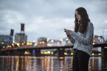 Woman using phone while standing against Burlington Northern Railroad Bridge 9.6 - CAVF33039