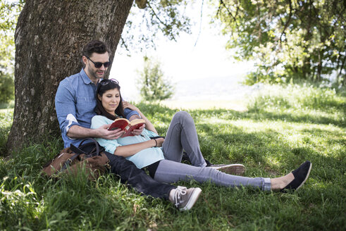 Couple reading book while relaxing by tree in park - CAVF33051
