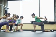 Instructor guiding women in exercising with dumbbells at health club - CAVF33126