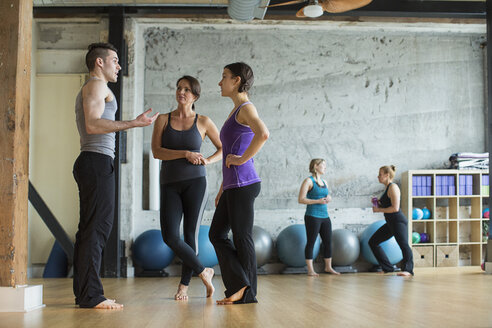 Male instructor guiding women in gym - CAVF33153