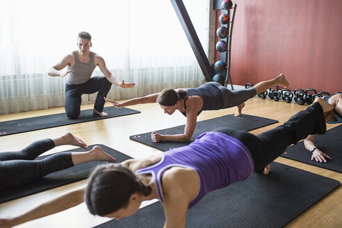 Male instructor guiding women in doing plank pose on exercise mats at gym - CAVF33159