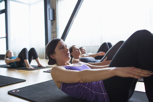 Male instructor with women exercising while lying on exercise mats in gym - CAVF33168