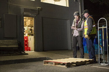 Workers using tablet computer while standing by warehouse at night - CAVF33174