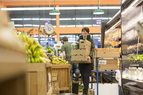 Female worker carrying boxes while working at supermarket - CAVF33186