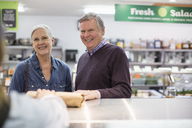 Cropped image of woman giving packet to senior couple at supermarket - CAVF33213