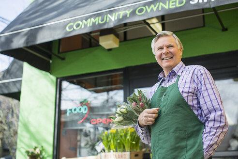 Senior male florist standing against flower shop - CAVF33216