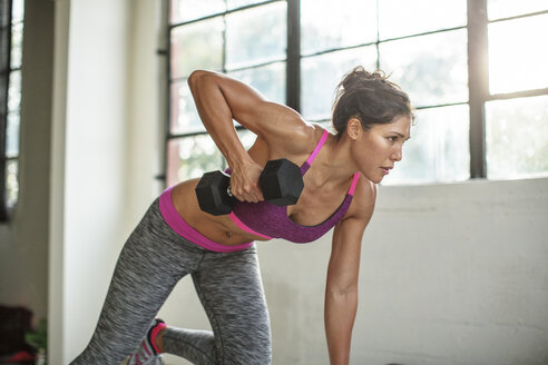 Female athlete lifting dumbbell while bending in gym - CAVF33267