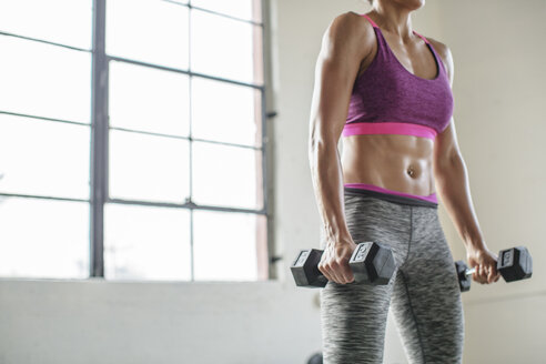 Midsection of female athlete lifting dumbbells in gym - CAVF33273