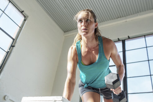 Low angle view of female athlete lifting dumbbell while doing push-ups in gym - CAVF33288