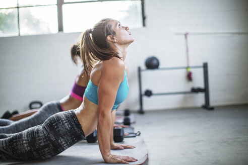 Female athletes practicing upward facing dog position in gym - CAVF33303