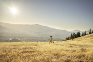 Side view of woman jogging on grassy field against sky during sunny day - CAVF33315