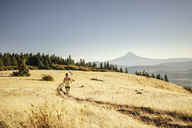 Rear view of woman jogging on mountain against sky during sunny day - CAVF33321