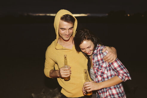Happy friends with arm around holding bottles while standing by river at night - CAVF33441