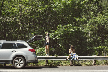 Female friends on railing by car against trees during sunny day - CAVF33444