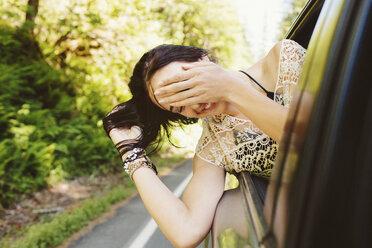 Happy woman peeking through window while traveling in car - CAVF33447