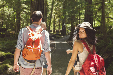 Portrait of woman hiking with friends on road in forest - CAVF33450