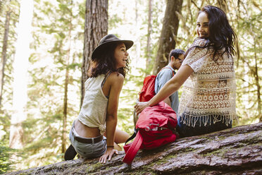 Portrait of smiling woman with friends enjoying in forest - CAVF33456