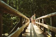 Friends walking on footbridge in forest - CAVF33459