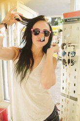Portrait of woman trying sunglasses at gas station - CAVF33471