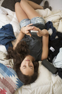 High angle view of woman using smart phone while lying on bed at home - CAVF33483