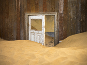 Africa, Namibia, inside a house of ghost town Kolmanskop, wooden door and sand - RJ00755