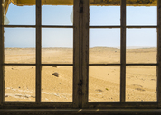 Africa, Namibia, Ghost town Kolmanskop, view through old window to namib desert - RJF00758