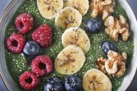 Buddha bowl of green chia pudding with slices of banana, blueberries, raspberries and walnuts - RTBF01143