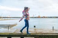 Azores, Sao Miguel, Woman walking on top of stone bench in Ponta Delgada harbor - KIJF01912