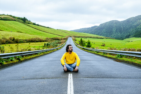 Azores, Sao Miguel, Man sitting on an empty road - KIJF01915