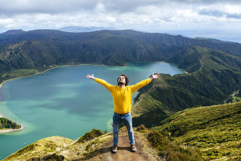 Azores, Sao Miguel, Man with raised arms and closed eyes on the top of the Lagoa do Fogo - KIJF01918