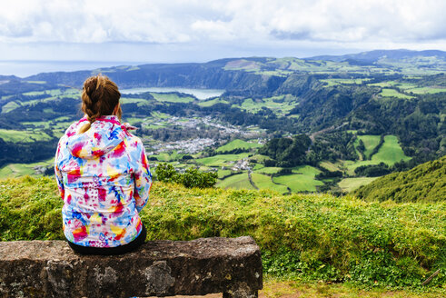 Azores, Sao Miguel, Woman sitting on stone bench looking towards the city and lake Furnas - KIJF01924