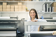 Portrait of smiling young woman standing by printing press - FOLF06696
