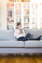 Girl sitting on couch at home holding cell phone - LVF06849
