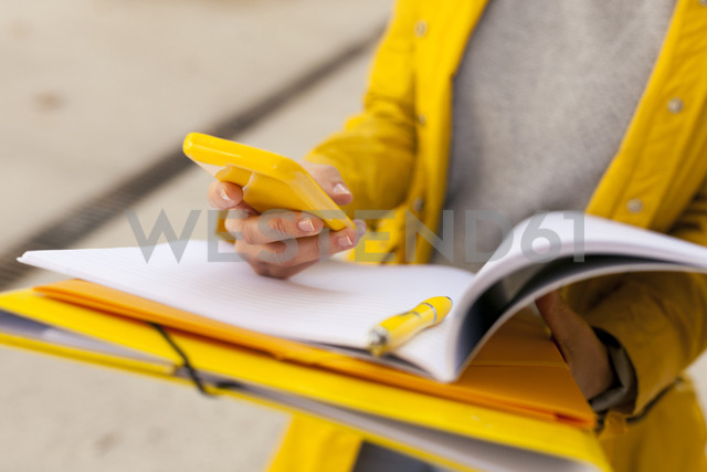 Close-up of woman with cell phone and folder outdoors - VABF01533 - Valentina Barreto/Westend61