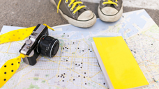 Close-up of sneakers, book and camera on city map - VAB01542