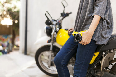 Close-up of woman with camera leaning against motorbike - VABF01545