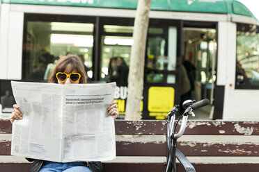 Woman wearing funny sunglasses reading newspaper on bench in the city - VABF01548