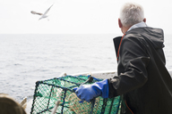 Man holding cage on boat and looking at sea - FOLF06958