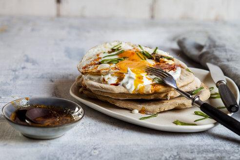 Flat bread with garlic yogurt, fried egg and chilli butter on chopping board - SBDF03511