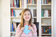 Portrait of happy girl tinkering with paper at home - LVF06856