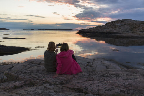 Mid adult women taking pictures on rocky seashore at sunset - FOLF07069