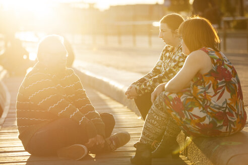Woman with down syndrome sitting on promenade with friends at sunset - FOLF07237