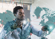 Casual businessman touching glass pane with world map in office - UUF13188