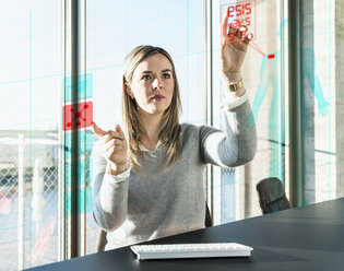 Young businesswoman touching projection screen with data in office - UUF13194