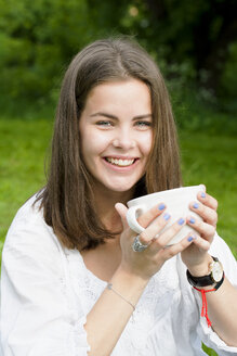 Portrait of young woman drinking from cup in park - FOLF07616