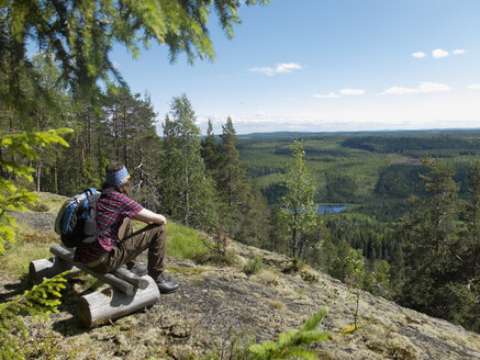 Hiker sitting on wooden bench in forest and looking at view - FOLF07643