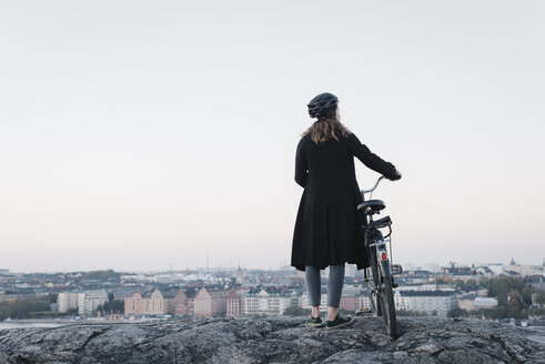 Rear view of young woman standing by bicycle on rock - FOLF07703