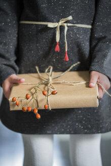 Girl holding wrapped Christmas present - FOLF07739