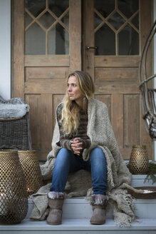 Blonde woman wrapped in plaid sitting on house porch - FOLF07745