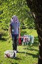 Man standing by drying rack with laundry on his head - FOLF07808
